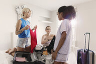 Young women friends packing for spring break in apartment bedroom - CAIF22710