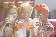 Young women friends drinking cocktails and taking selfie with smart phone in sunny bar - CAIF22737