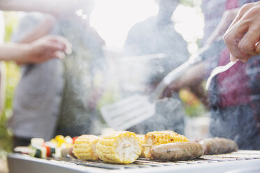 Corncobs, sausages and vegetable skewers cooking on barbecue grill - CAIF22743