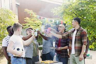 Happy male friends toasting drinks over barbecue grill in backyard - CAIF22746