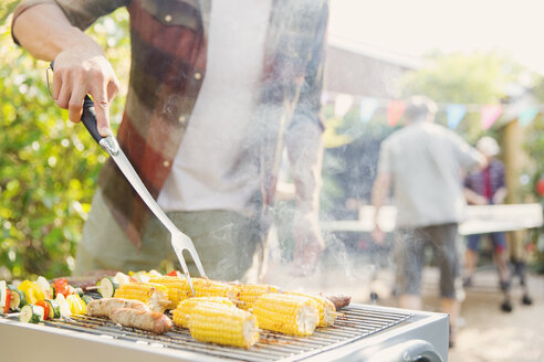 Man barbecuing corn, sausage and vegetable kebabs - CAIF22749