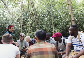 Mens group with map preparing for hike in woods - CAIF22758