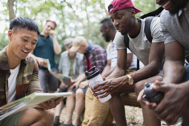 Men friends looking at hiking map in woods - CAIF22761