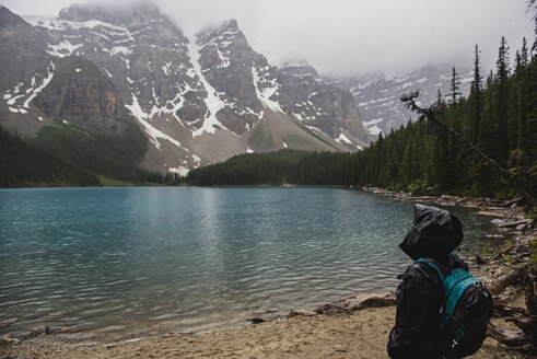 Serene hiker in rain jacket enjoying tranquil mountain and lake view, Banff, Alberta, Canada - CAIF22770