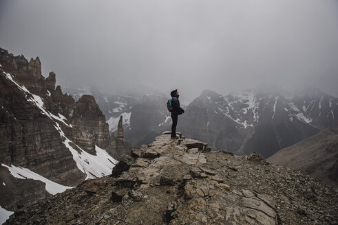 Female hiker on top of craggy, foggy mountain Banff, Alberta, Canada - CAIF22773