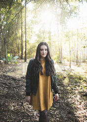Portrait of teenage girl with long hair standing against trees in forest - CAVF61073