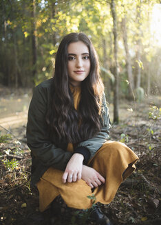 Portrait of confident teenage girl with long hair crouching against trees in forest - CAVF61076