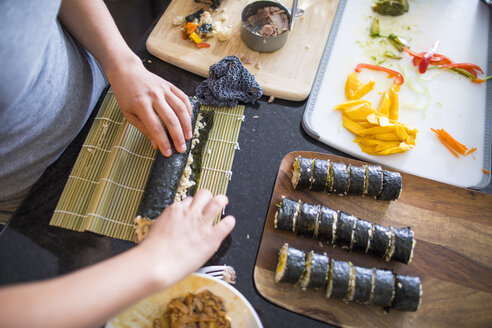 High angle midsection of woman making sushi on kitchen island at home - CAVF61082