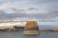 Scenic view of Lake Powell by cliffs against cloudy sky during sunset - CAVF61094
