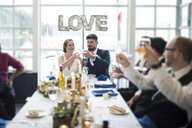 Newlywed couple toasting drinks while having lunch with family in restaurant - CAVF61124