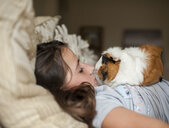 Side view of girl with guinea pig lying on bed at home - CAVF61133