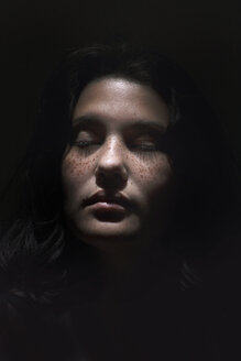 Close-up of teenage girl with eyes closed against black background - CAVF61145
