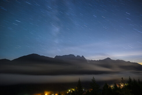 Scenic view of mountains against star trails at night - CAVF61202