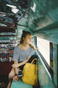Female tourist with backpack looking through window while travelling in motor home - CAVF61205