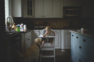 Baby girl with mouth open looking at dog while sitting on high chair in kitchen - CAVF61217