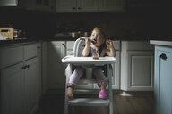 Cute baby girl eating food while sitting on high chair in kitchen at home - CAVF61220