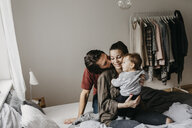 Happy family with baby girl sitting on bed at home - LHPF00466