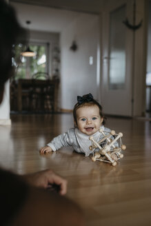 Happy baby girl lying on the floor playing with motor skill toy - LHPF00478