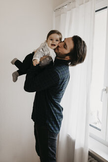 Father carrying baby girl at home - LHPF00484
