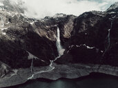 Scenic view of waterfall amidst mountains against cloudy sky during winter - CAVF61242