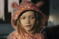 Close-up of thoughtful girl in pink hooded jacket looking away while sitting at home - CAVF61320