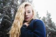 Low angle portrait of woman with blond hair standing against trees in forest during winter - CAVF61341