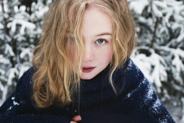 Close-up portrait of woman with blond hair standing against trees in forest during winter - CAVF61344