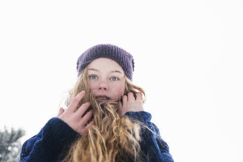 Low angle portrait of woman with blond hair standing against clear sky during winter - CAVF61347