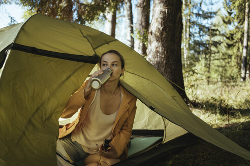Female hiker drinking drink while sitting in tent at forest - CAVF61377