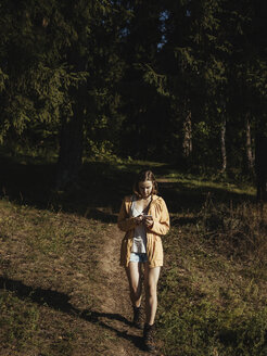 Full length of female hiker using mobile phone while walking in forest during sunny day - CAVF61386