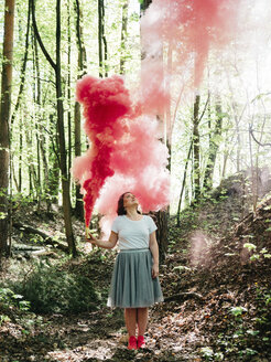 Full length of woman with red smoke grenade standing in forest - CAVF61395