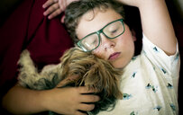 High angle view of boy with Yorkshire Terrier sleeping at home - CAVF61398