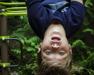 Close-up portrait of cute boy hanging upside down against trees at park - CAVF61410