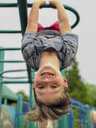 Close-up portrait of cute smiling boy hanging upside down on jungle gym against sky at park - CAVF61413