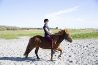 Woman horseback riding on sand at beach during sunny day - CAVF61425