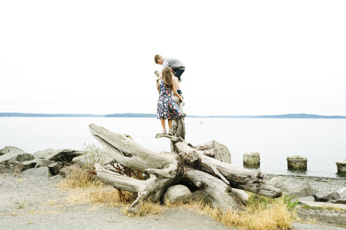 Playful siblings climbing on logs at beach against clear sky - CAVF61437