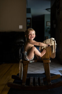 Side view of cheerful baby girl sitting on wooden rocking horse at home - CAVF61467