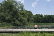 Rear view of shirtless boy sitting on pier over lake against sky in forest - CAVF61473