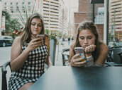 Female friends using smart phones while sitting at sidewalk cafe - CAVF61485