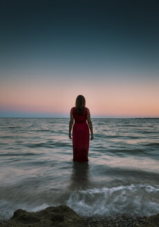 Rear view of woman standing in sea against clear sky during sunset - CAVF61488