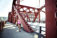 Female athlete running on footbridge in city - CAVF61521