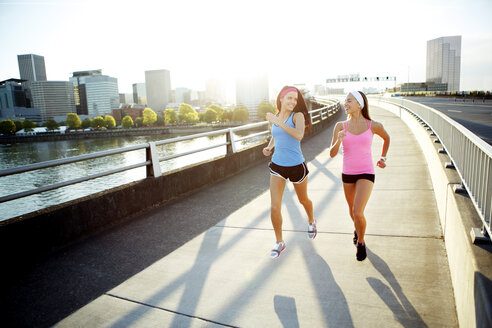 Female athlete friends talking while running on bridge against sky in city during sunny day - CAVF61527