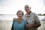 Portrait of senior couple standing at beach against sky - CAVF61539