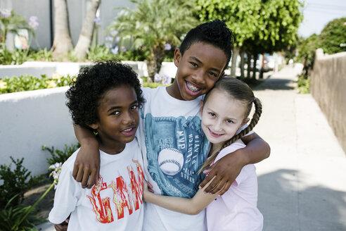 Portrait of smiling siblings standing on footpath in city - CAVF61542