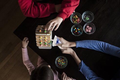 High angle view of siblings making gingerbread house together on table at home - CAVF61557