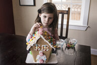 Cute girl decorating gingerbread house on table at home - CAVF61560