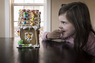 Cute happy girl with finger in mouth looking at gingerbread house on table at home - CAVF61563