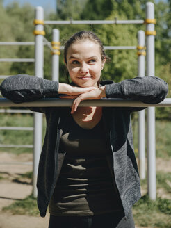 Smiling woman looking away while leaning on gymnastics bar at park during sunny day - CAVF61575