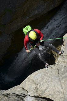 High angle view of male hiker rappelling on Pyrenees over waterfall - CAVF61581