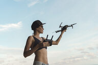 Woman holding drone under sky with clouds - KNTF02708